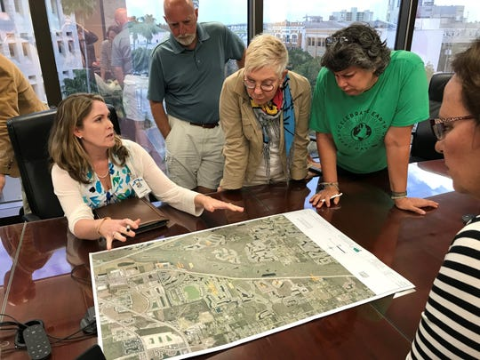 Ecologist Bethany Brosious explains to concerned residents that the site of a proposed new fire station in Fort Myers is about half covered with exotic plants.
