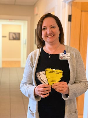 """Tanya Fischer, dental clinic director, displays some of the """"teeth"""" available to purchase during the Tooth Fairy Fundraiser."""