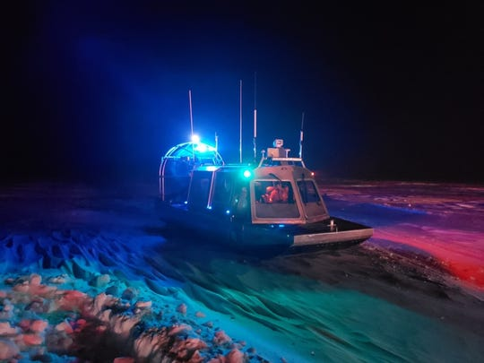 United States Coast Guard airboat rescues individuals on the ice in Sturgeon Bay.