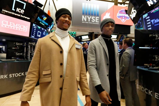 Clemson University football players Isaiah Simmons, left, and Tee Higgins walk the trading floor before ringing the New York Stock Exchange closing bell, Wednesday Jan. 30, 2019, to celebrate winning the 2019 College Football Playoff National Championship. (AP Photo/Richard Drew)