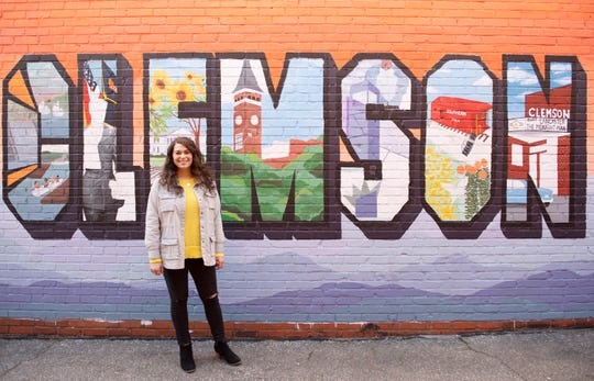 Clemson junior Arianna Conti next to the mural that is a work in progress in downtown Clemson Thursday, Jan. 31, 2019.
