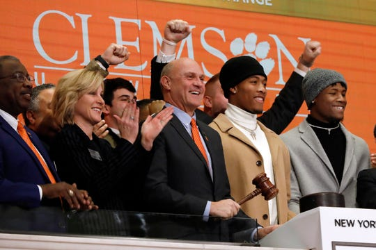 Clemson University football players Isaiah Simmons, second from right, and Tee Higgins, right, joined by Clemson President Jim Clements, center, ring the New York Stock Exchange closing bell, Wednesday Jan. 30, 2019, to celebrate winning the 2019 College Football Playoff National Championship. (AP Photo/Richard Drew)