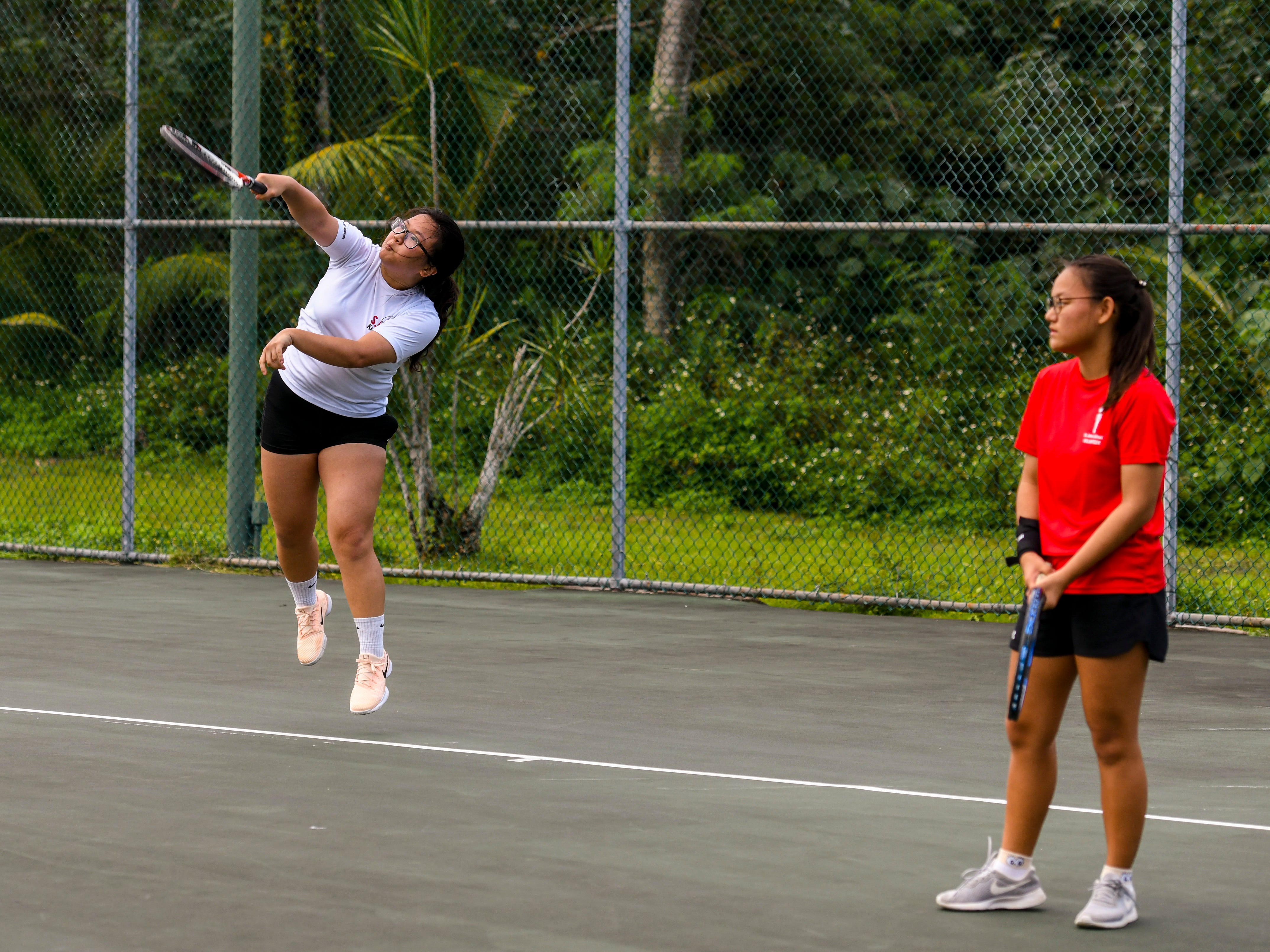 St. John's Knights' Aprile Kim slams one over the net as she and doubles teammate, Rachel Seo, take on challengers from the Academy of Our Lady Guam Cougars during an Interscholastic Athletic Association of Guam tennis match at the Rick Ninete Tennis Center in Hagåtna on Thursday, Jan. 31, 2019.