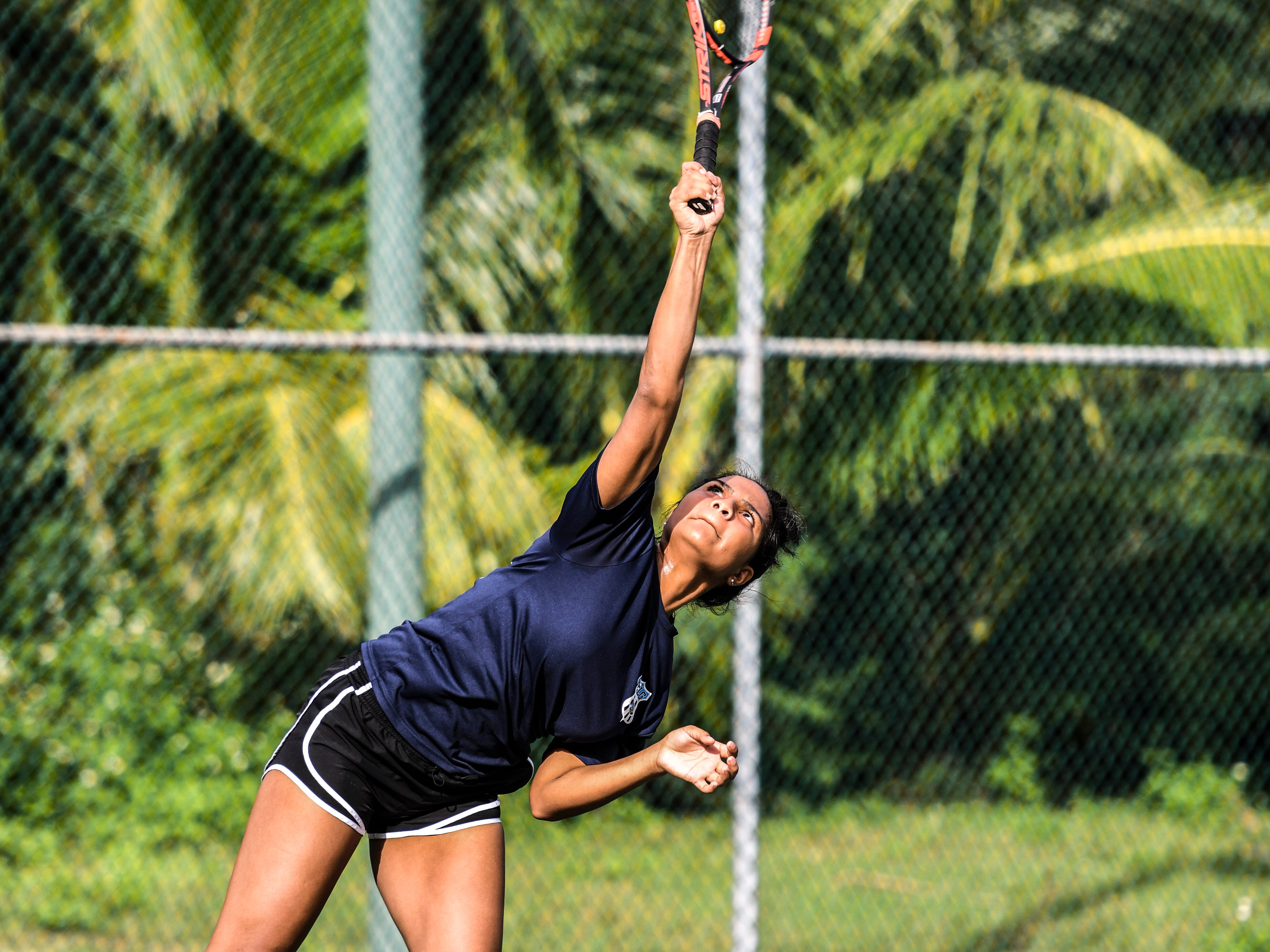 Academy of Our Lady Guam Cougars' Jocelyn Tenai asserts power behind a serve during an Interscholastic Athletic Association of Guam tennis singles match with St. John's Knights' Anika Sachdev at the Rick Ninete Tennis Center in Hagåtna on Thursday, Jan. 31, 2019.
