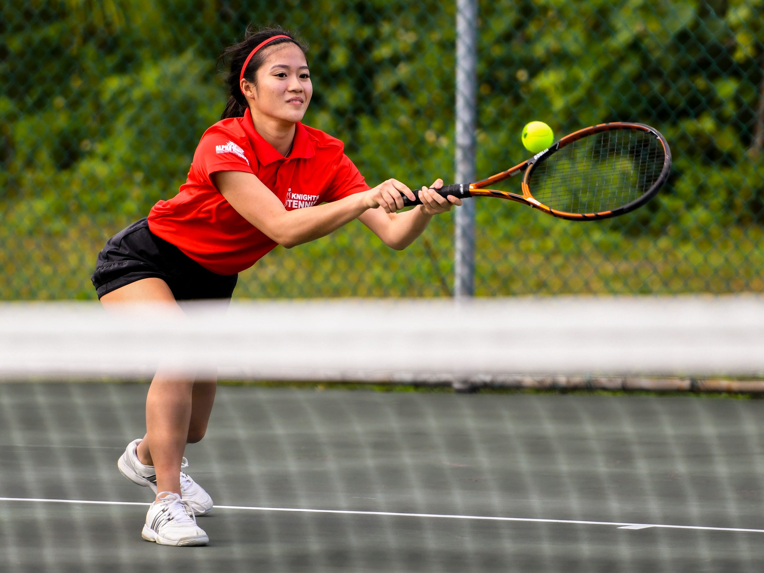 St. John's Knights' Ayaka Lin stretches out to return a volley during an Interscholastic Athletic Association of Guam tennis singles match against Academy of Our Lady Guam Cougars' Mika Alcantara at the Rick Ninete Tennis Center in Hagåtna on Thursday, Jan. 31, 2019.