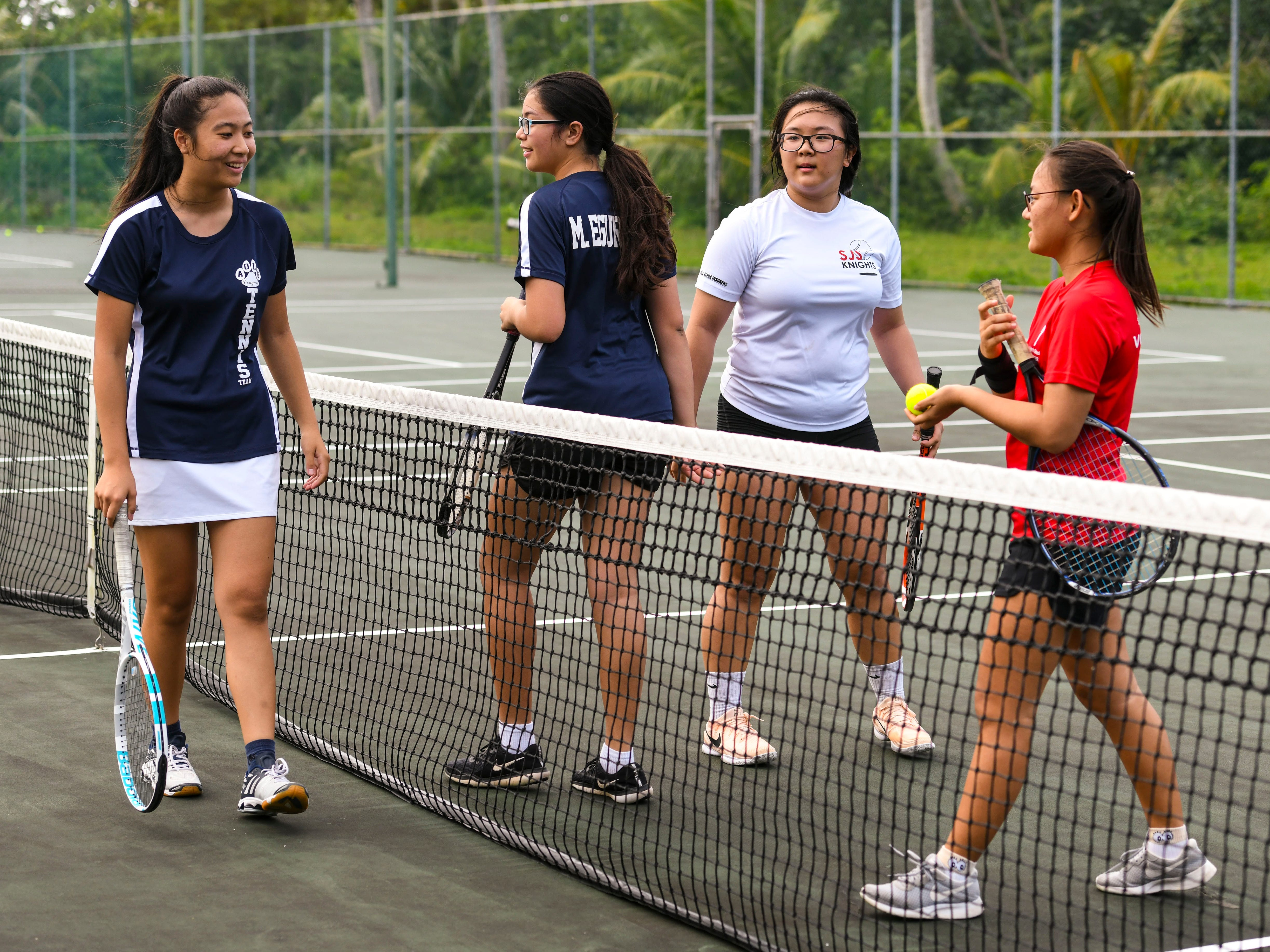 St. John's Knights and Academy of Our Lady Guam Cougars players congratulate one another after completing an Interscholastic Athletic Association of Guam tennis doubles match at the Rick Ninete Tennis Center in Hagåtna on Thursday, Jan. 31, 2019.