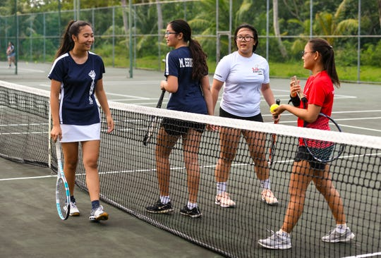 Players from the St. John's Knights and Academy of Our Lady Guam Cougars congratulate one another after an IIAAG Tennis doubles match at the Rick Ninete Tennis Center in Hagåtna in this Jan. 31 file photo.