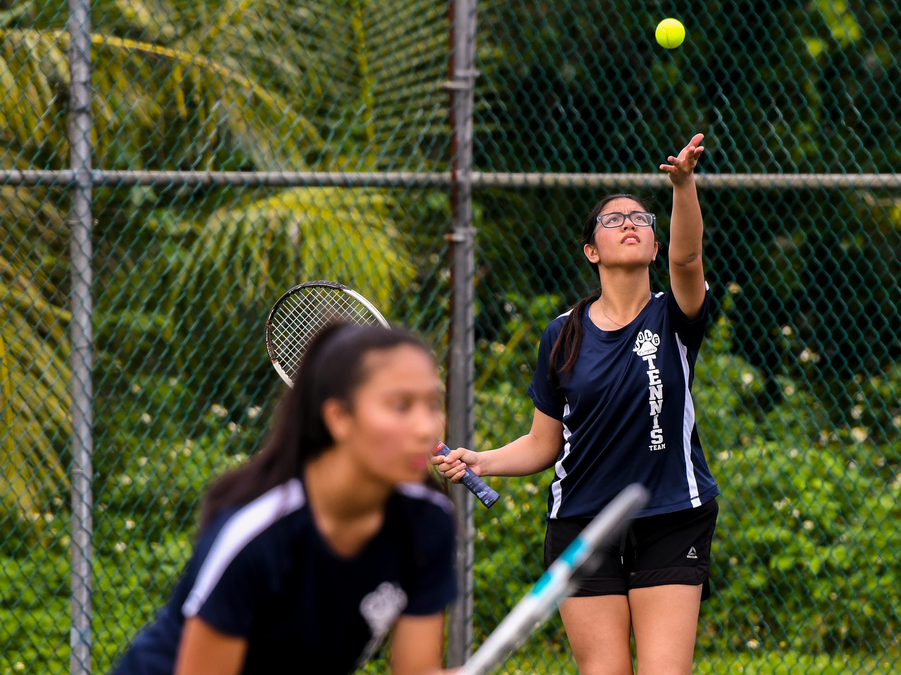 Academy of Our Lady Guam Cougars' Maria Egurrola prepares to serve as she and doubles teammate, Andrea Cruz, take on challengers from the St. John's Knights during an Interscholastic Athletic Association of Guam tennis match at the Rick Ninete Tennis Center in Hagåtna on Thursday, Jan. 31, 2019.