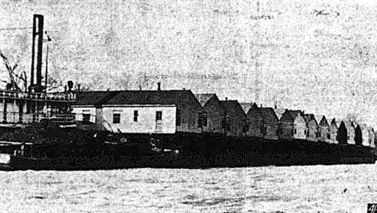 A barge tow of 30 duplexes docked overnight in Louisville in mid-March 1944  because of high winds while they were being brought to Camp Breckinridge from Point Pleasant, West Virginia. They were part of 120 living units moved to alleviate the civilian housing shortage at the camp This photo appeared in The Gleaner of 3-18-1944. See Yesterday's News column of 2-3-2019 for greater detail.