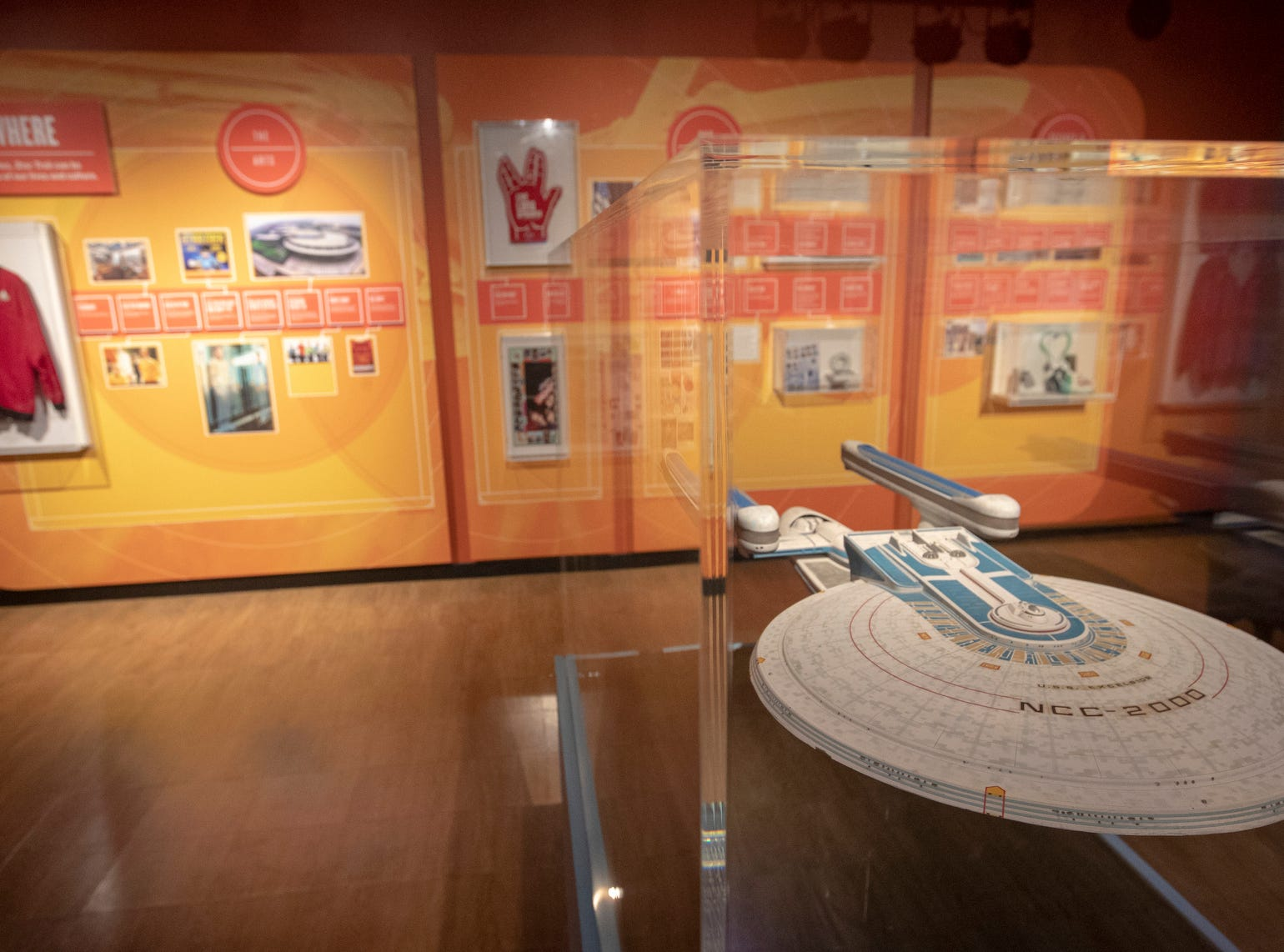 """A display showing various ways the Star Trek universe has inspired popular culture over the years -- with a model of a starship in the foreground -- is seen at The Children's Museum of Indianapolis, on Wednesday, Jan. 23, 2019. The """"Star Trek: Exploring New Worlds"""" exhibit is made up of set pieces, ship models, and outfits used during various Star Trek shows and movies and is on display at the museum from Feb. 2 through April 7, 2019."""