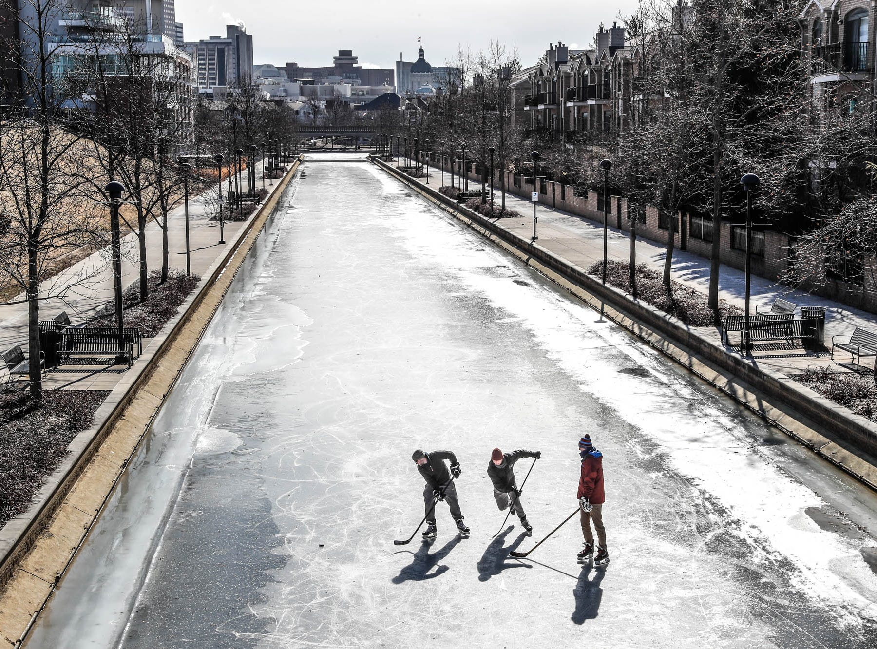 Left to right, friends Chase Fairchild, Charlie Hornett, and Jackson Richey get some free ice time to practice hockey skills on the downtown Indianapolis canal on Thursday, Jan. 31, 2019.