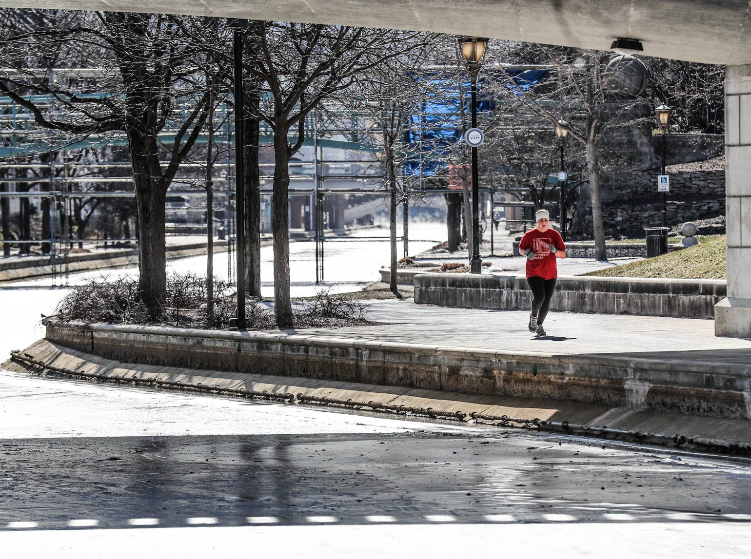 A woman jogs along on the canal in downtown Indianapolis on Thursday, Jan. 31, 2019.