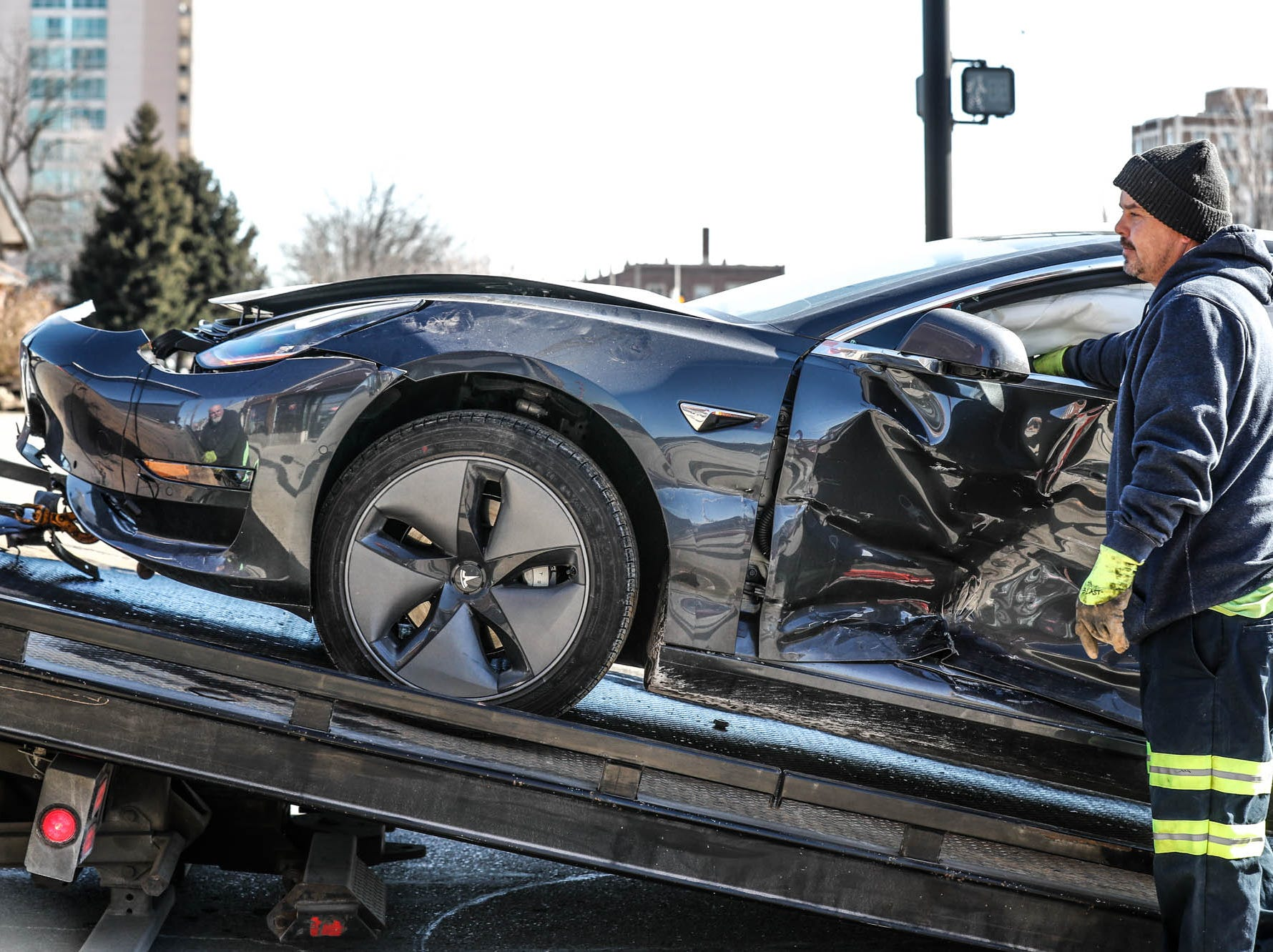 A tow truck driver loads a Tesla on a truck after a multi-vehicle crash at the intersection of Illinois Street and 38th St. included a Tesla on Thursday, Jan. 31, 2019. The Tesla's owner had waited over a year for the car and could be seen with tears running down his cheeks in the sub-zero temperatures.