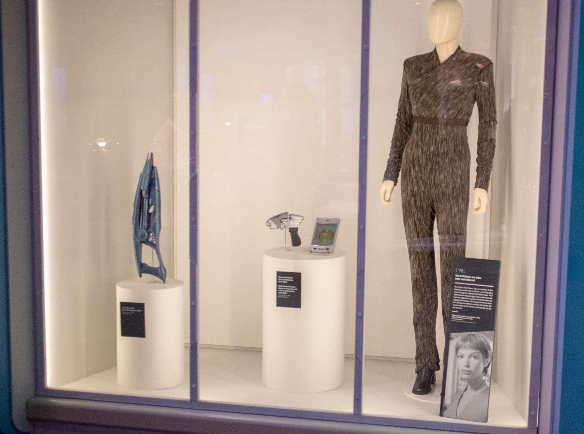"""A uniform worn by the Vulcan character T'Pol in the TV series """"Star Trek: Enterprise"""" is seen alongside Star Trek accessories at The Children's Museum of Indianapolis, Wednesday, Jan. 23, 2019. The """"Star Trek: Exploring New Worlds"""" exhibit is made up of set pieces, ship models and outfits used during various Star Trek shows and movies, and is on display at the museum from Feb. 2 through April 7, 2019."""