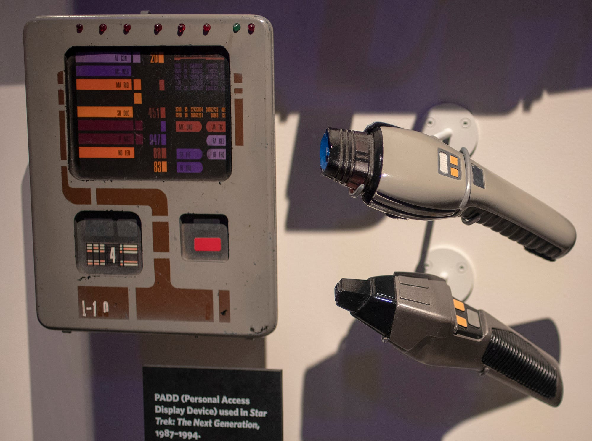 """An iPad-like computer called a personal access display device (left) and two phaser models, all from """"Star Trek: The Next Generation,"""" are seen at The Children's Museum of Indianapolis, Wednesday, Jan. 23, 2019. The """"Star Trek: Exploring New Worlds"""" exhibit is made up of set pieces, ship models and outfits used during various Star Trek shows and movies and is on display at the museum from Feb. 2 through April 7, 2019."""