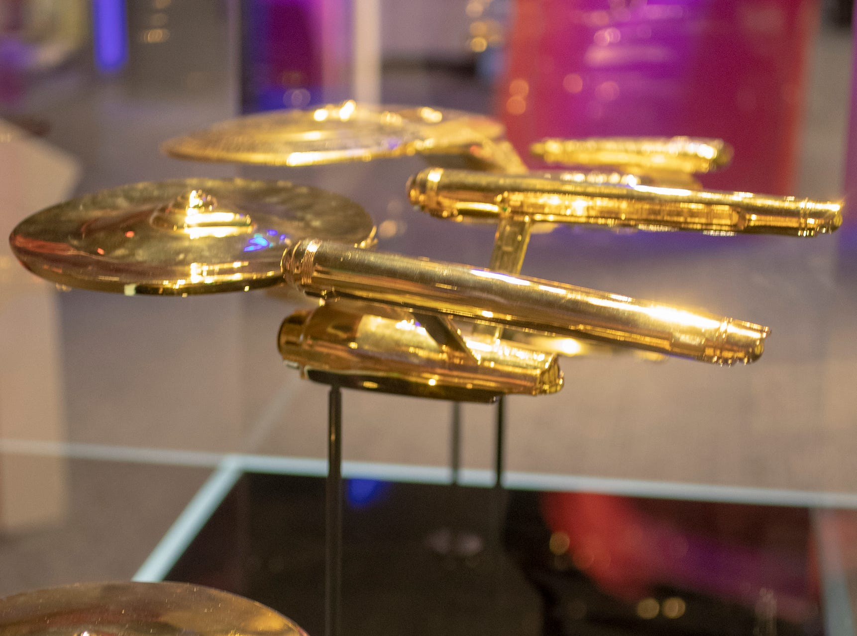 """Golden starship models are seen at The Children's Museum of Indianapolis, Wednesday, Jan. 23, 2019. The """"Star Trek: Exploring New Worlds"""" exhibit is made up of set pieces, ship models and outfits used during various Star Trek shows and movies and is on display at the museum from Feb. 2 through April 7, 2019."""
