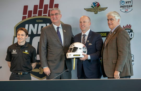 Dignitaries from left, Zach Veach, Andretti Autosport driver, Eric Holcomb, Governor of Indiana, Dan Towriss, Group1001 President and CEO, and Mark Miles, President and CEO of Hulman and Company pose for photos after an announcement at the Indianapolis Motor Speedway about the partnership of Indy 500 title sponsor Gainbridge, Indianapolis, Thursday, Jan. 31, 2019.
