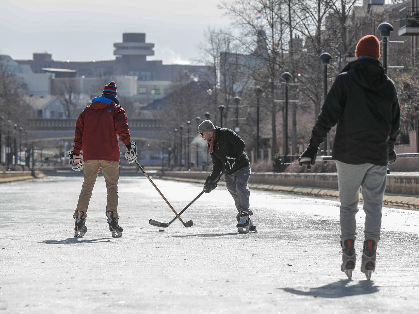 Friends Jackson Richey,  Chase Fairchild, and Charlie Hornett get some free ice time to practice hockey skills on the downtown Indianapolis canal on Thursday, Jan. 31, 2019.