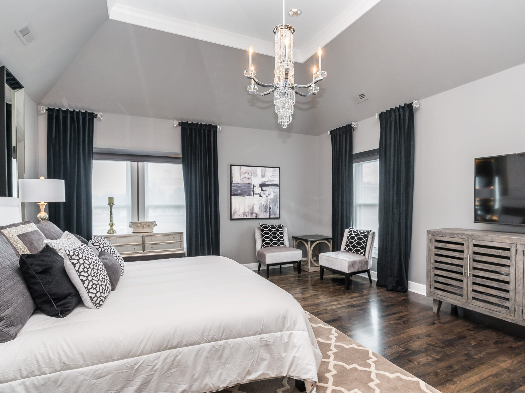 The master bedroom includes a small sitting area and 60-inch flatscreen television.