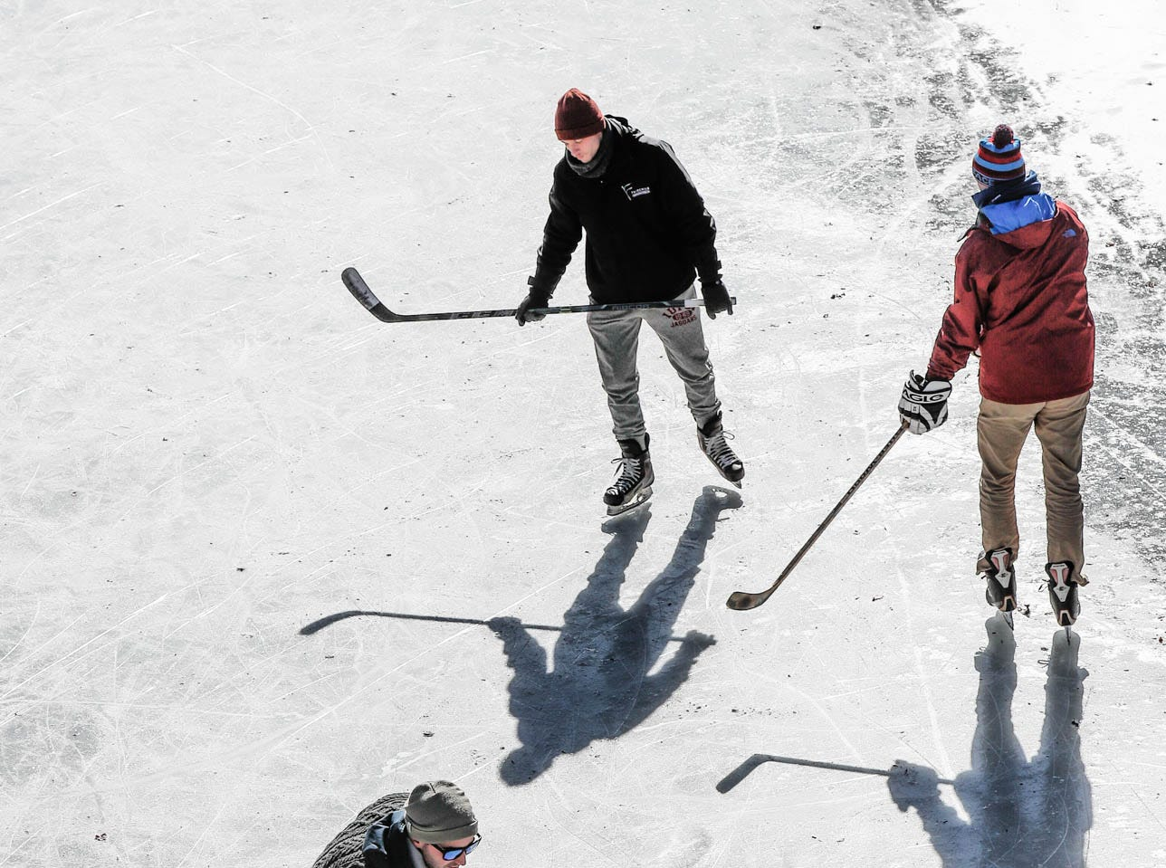 Left to right, friends Chase Fairchild, Charlie Hornett, and Jackson Richey, get some free ice time to practice hockey skills on the downtown Indianapolis canal on Thursday, Jan. 31, 2019.