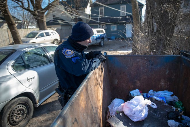 IMPD Sgt. Bill Carter looks at a dead dog placed in a dumpster behind an apartment on East 10th Street, Indianapolis, Wednesday, Jan. 30, 2019. The dog had died the previous evening while exposed to subzero temperatures in an outdoor kennel.