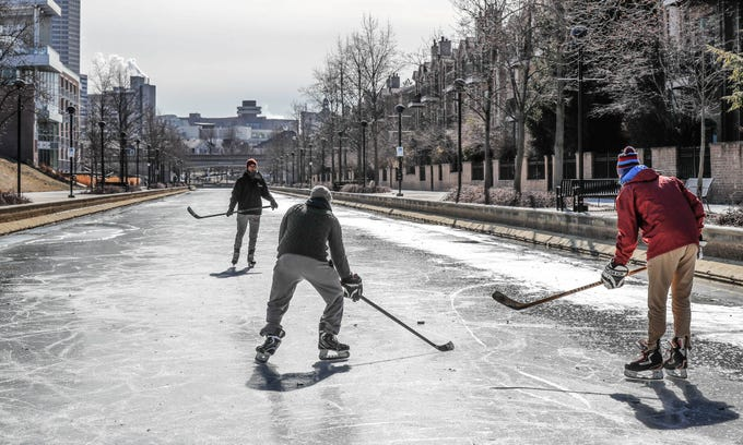 Left to right, friends  Charlie Hornett, Chase Fairchild , and Jackson Richey get some free ice time to practice hockey skills on the downtown Indianapolis canal on Thursday, Jan. 31, 2019.