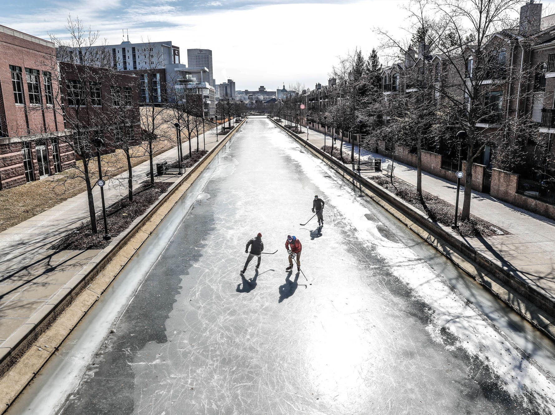 Left to right, friends Charlie Hornett, Jackson Richui, and Chase Fairchild get some free ice time to practice hockey skills on the downtown Indianapolis canal on Thursday, Jan. 31, 2019.