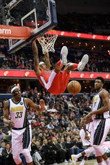 Washington Wizards guard Bradley Beal, center, hangs on to the rim after his dunk against Indiana Pacers center Myles Turner (33) and forward Thaddeus Young (21).