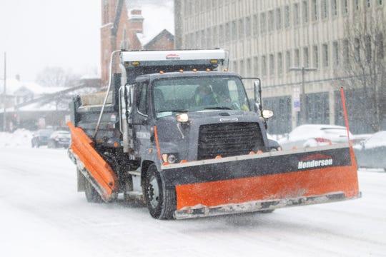 A snow plow drives down Clinton Street as snow falls on Thursday, Jan. 31, 2019, in downtown Iowa City, Iowa.
