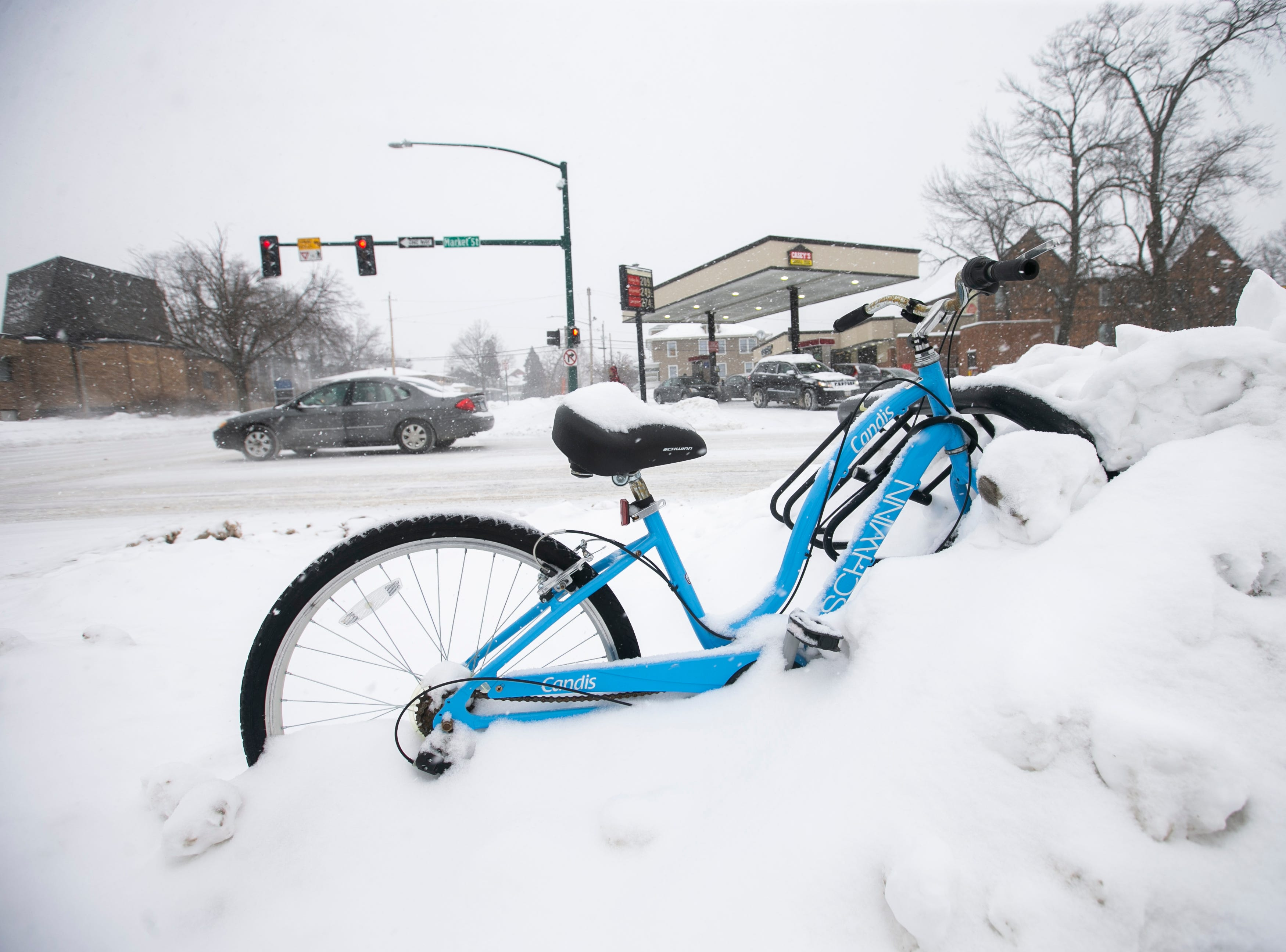 A bicycle gets packed in with snow as snow falls on Thursday, Jan. 31, 2019, in downtown Iowa City, Iowa.