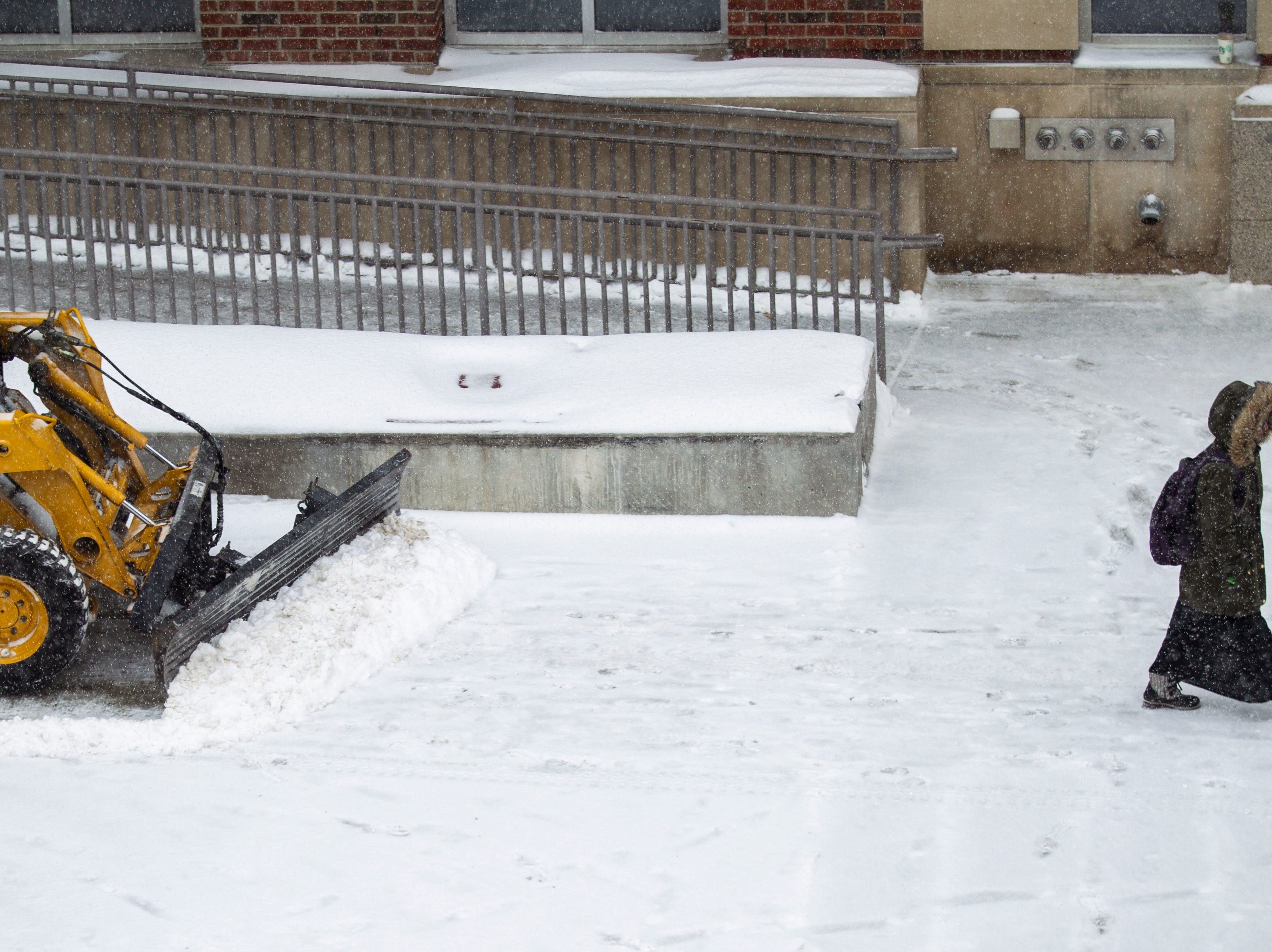 A person walks on the sidewalk while being followed by a plow as snow falls on Thursday, Jan. 31, 2019, in downtown Iowa City, Iowa.