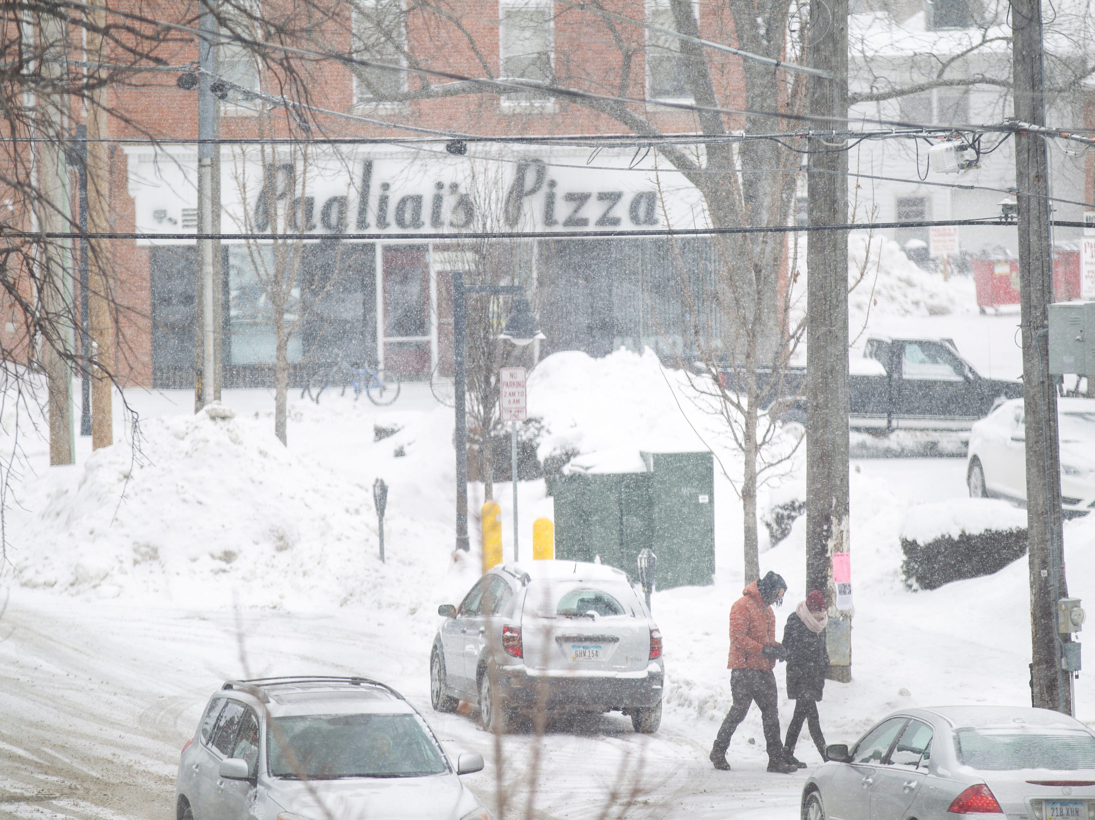 People walk as snow falls on Thursday, Jan. 31, 2019, in downtown Iowa City, Iowa.