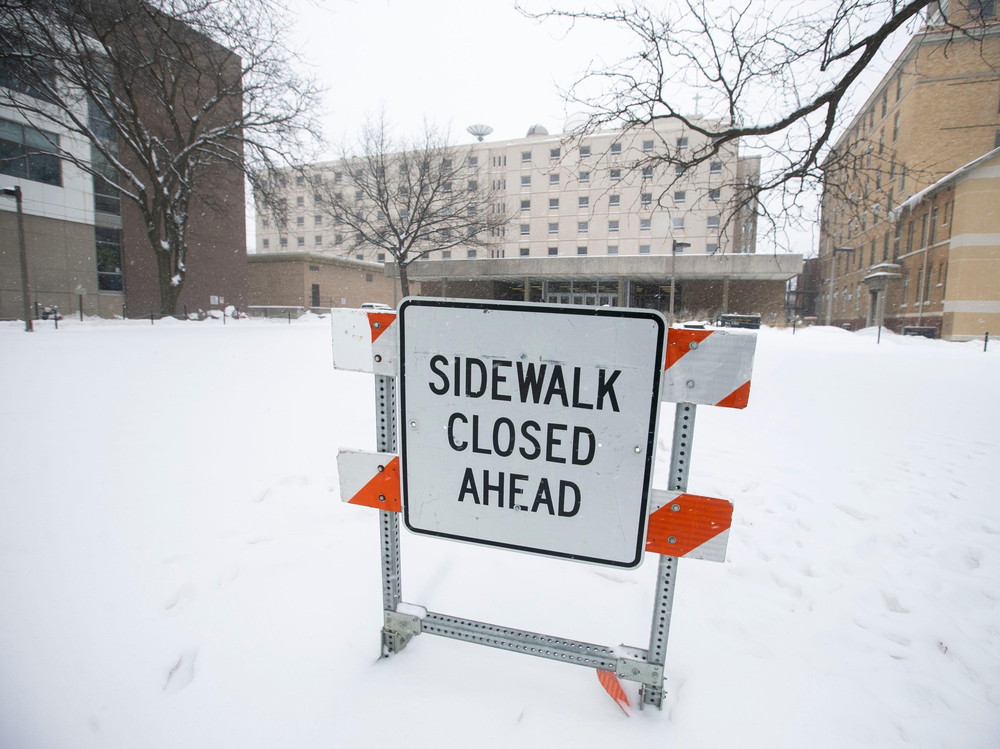A sign along Iowa Avenue is seen as snow falls on Thursday, Jan. 31, 2019, in downtown Iowa City, Iowa.