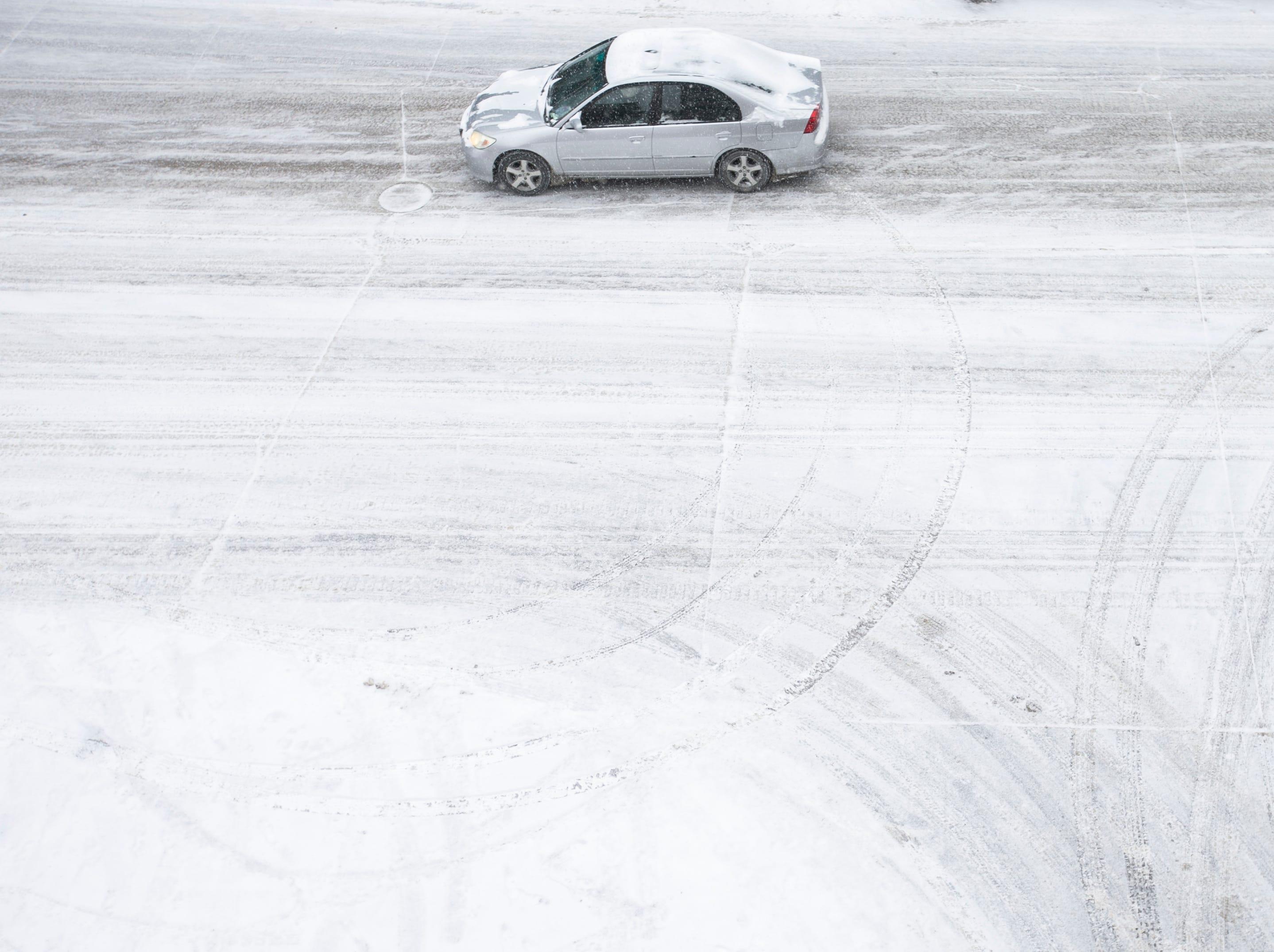 A car drives along Madison Street as snow falls on Thursday, Jan. 31, 2019, in downtown Iowa City, Iowa.