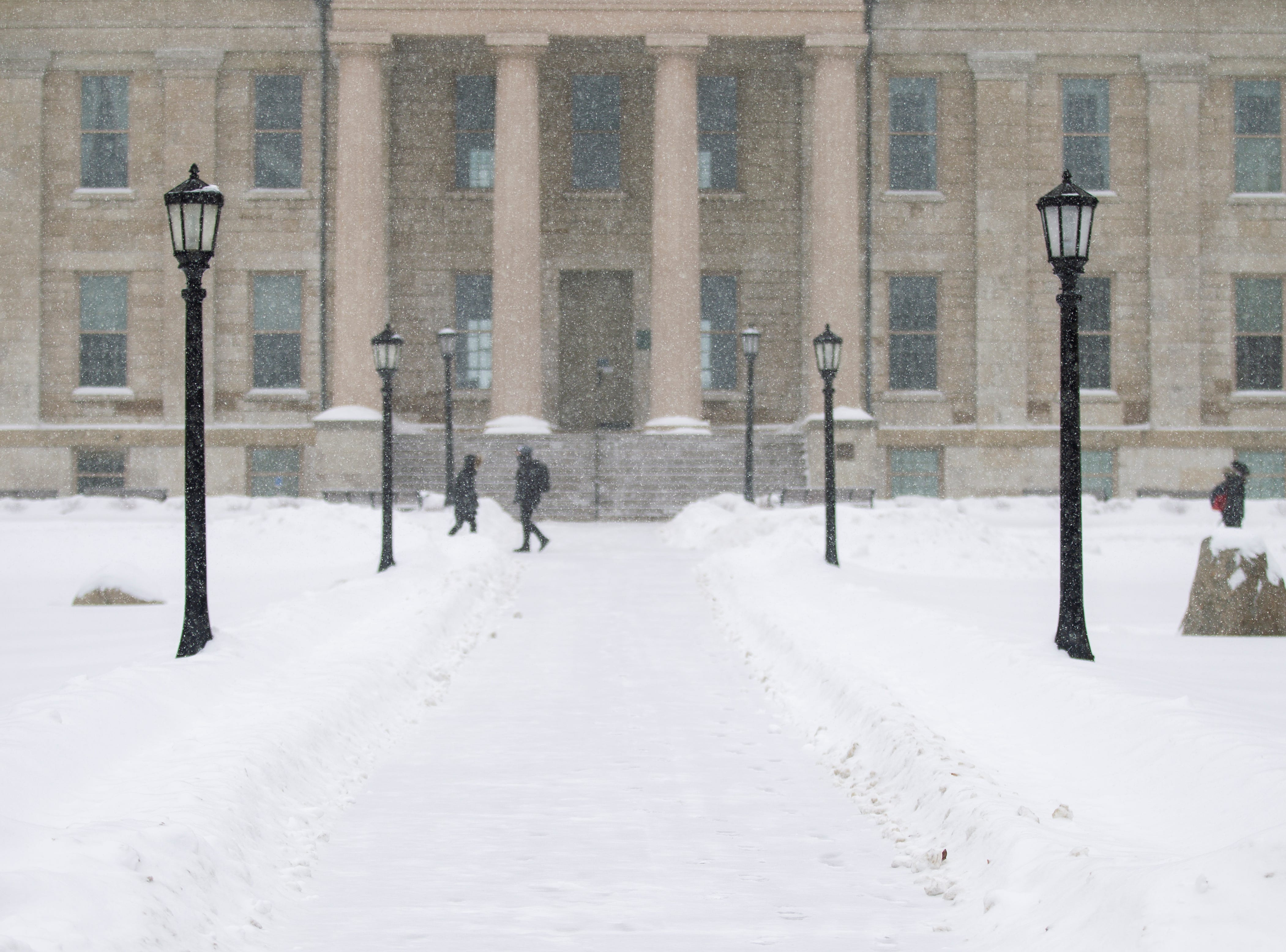 Students walk past the Old Capitol Building as snow falls on Thursday, Jan. 31, 2019, in downtown Iowa City, Iowa.