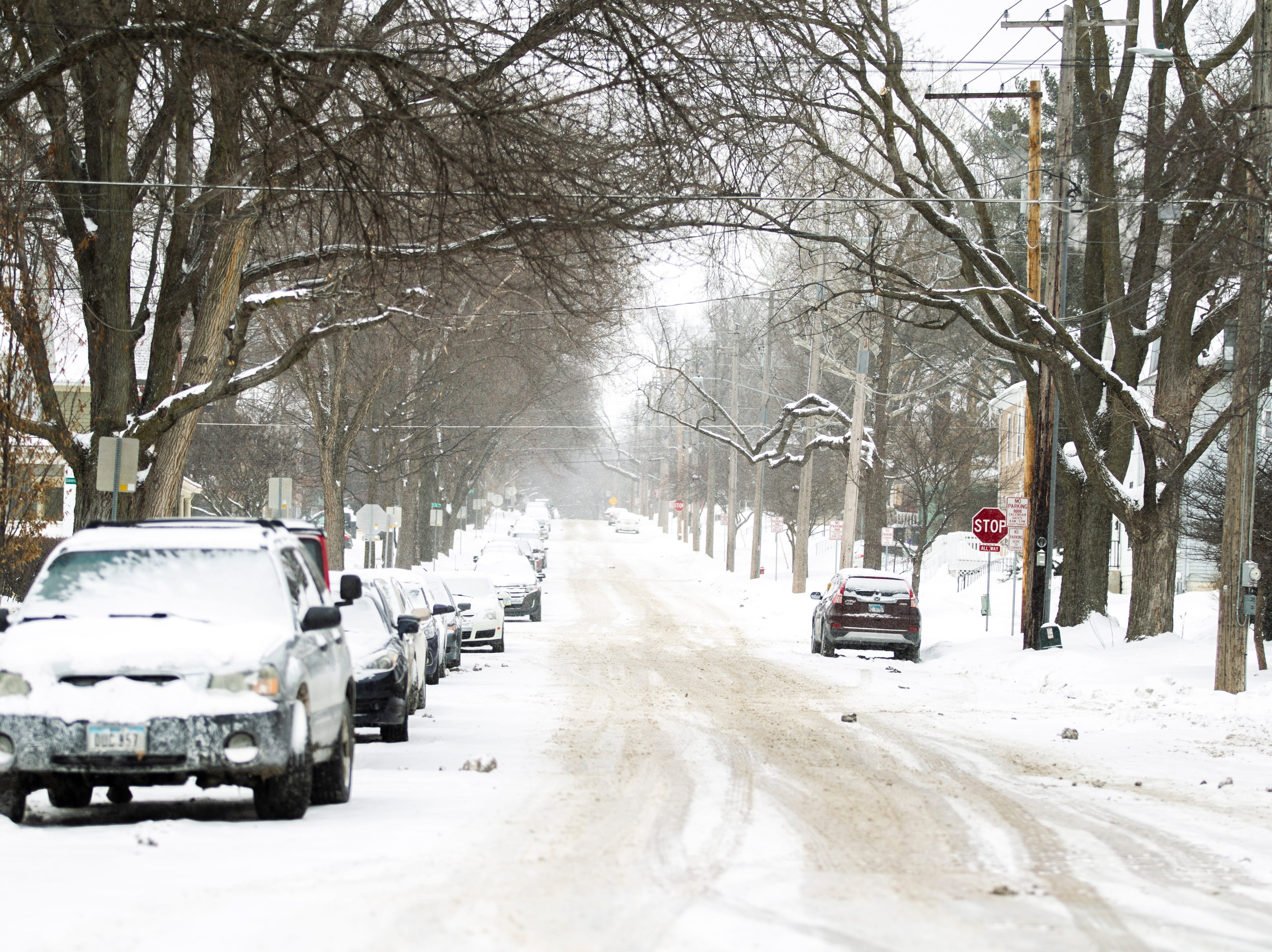 Cars park on opposite sides of the street as snow falls on Thursday, Jan. 31, 2019, along North Linn Street in Iowa City, Iowa.