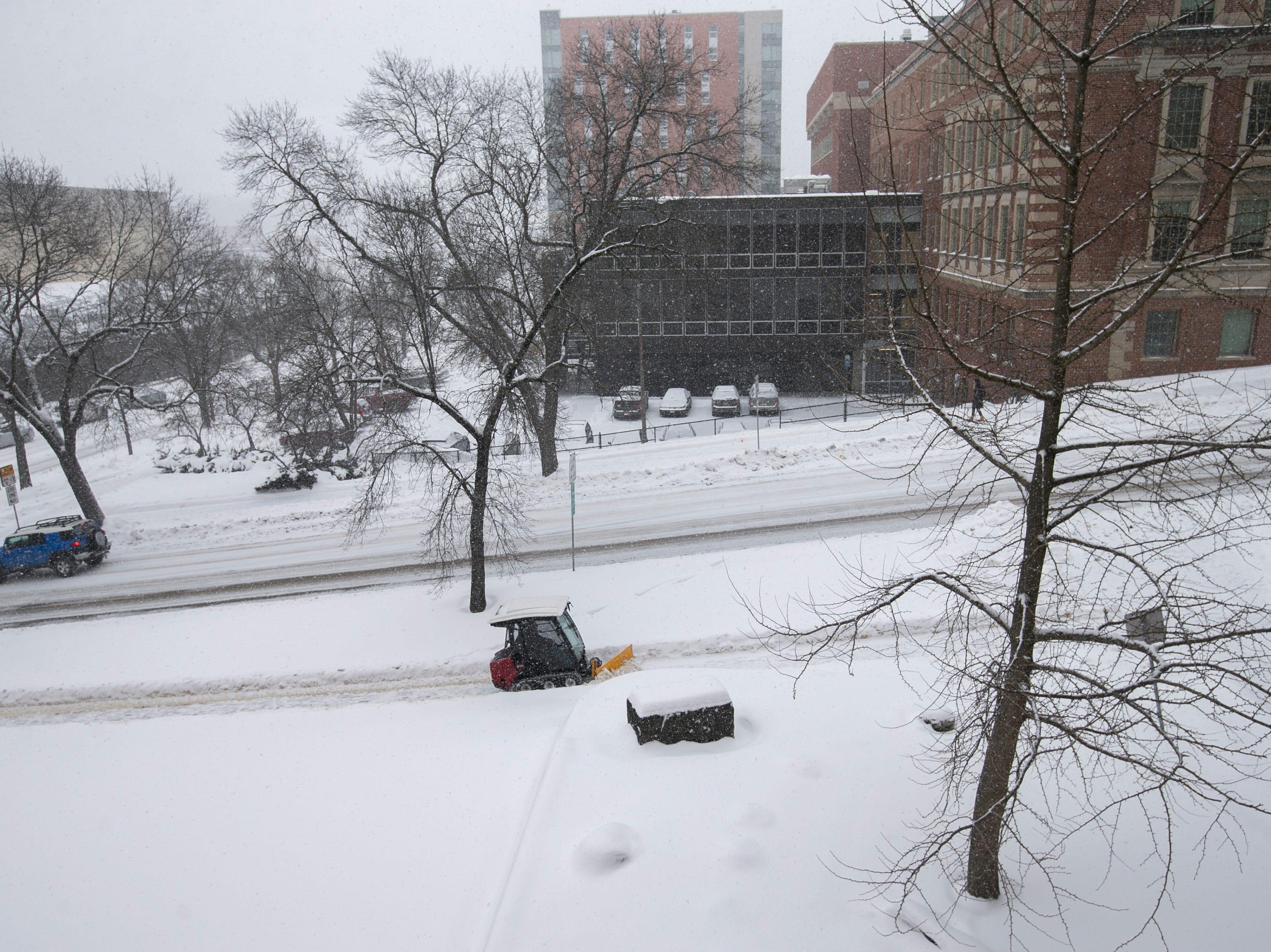 A small plow clears a sidewalk on Market Street as snow falls on Thursday, Jan. 31, 2019, in downtown Iowa City, Iowa.