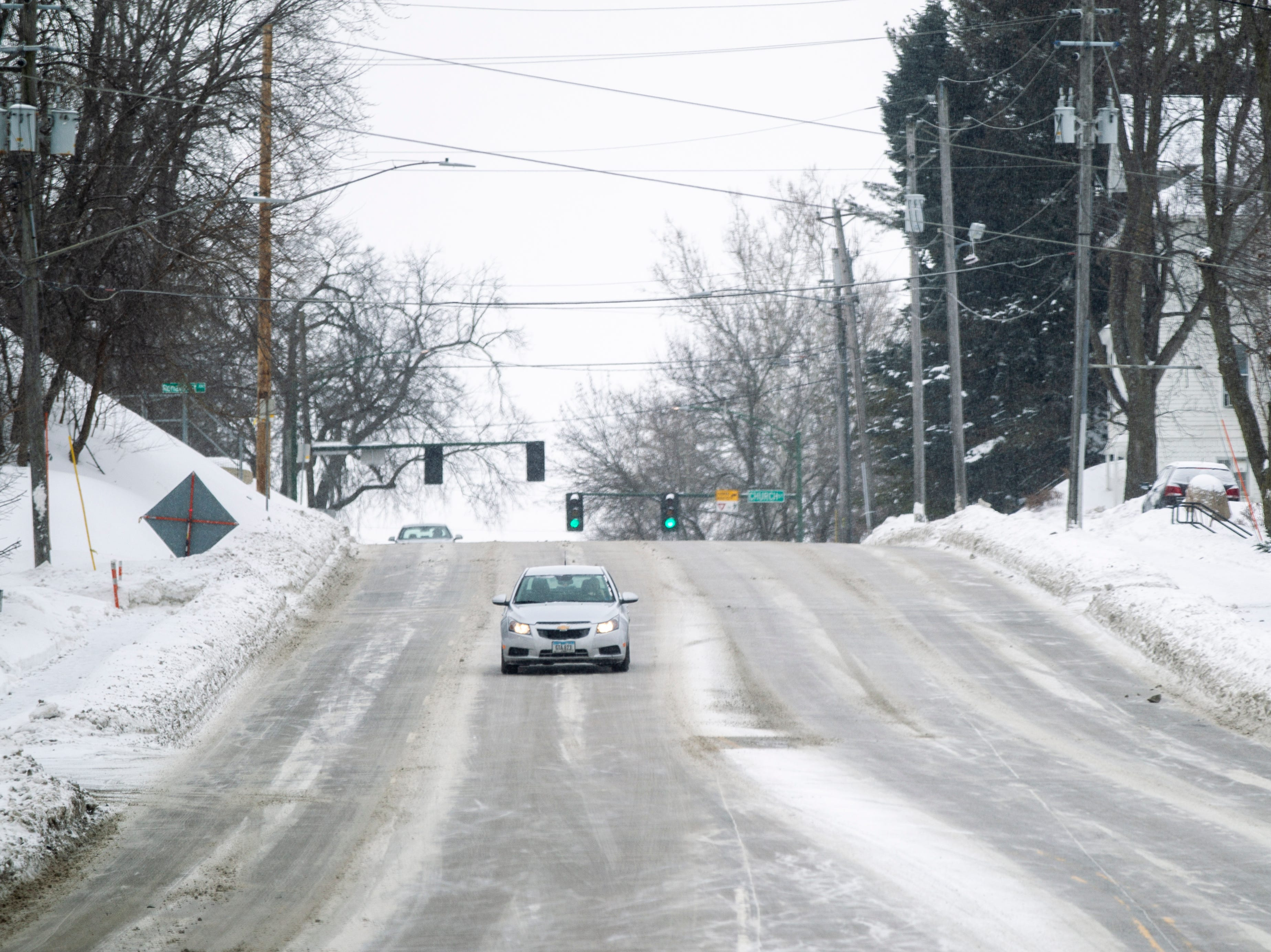 A car drives as snow falls on Thursday, Jan. 31, 2019, along North Dubuque Street in Iowa City, Iowa.