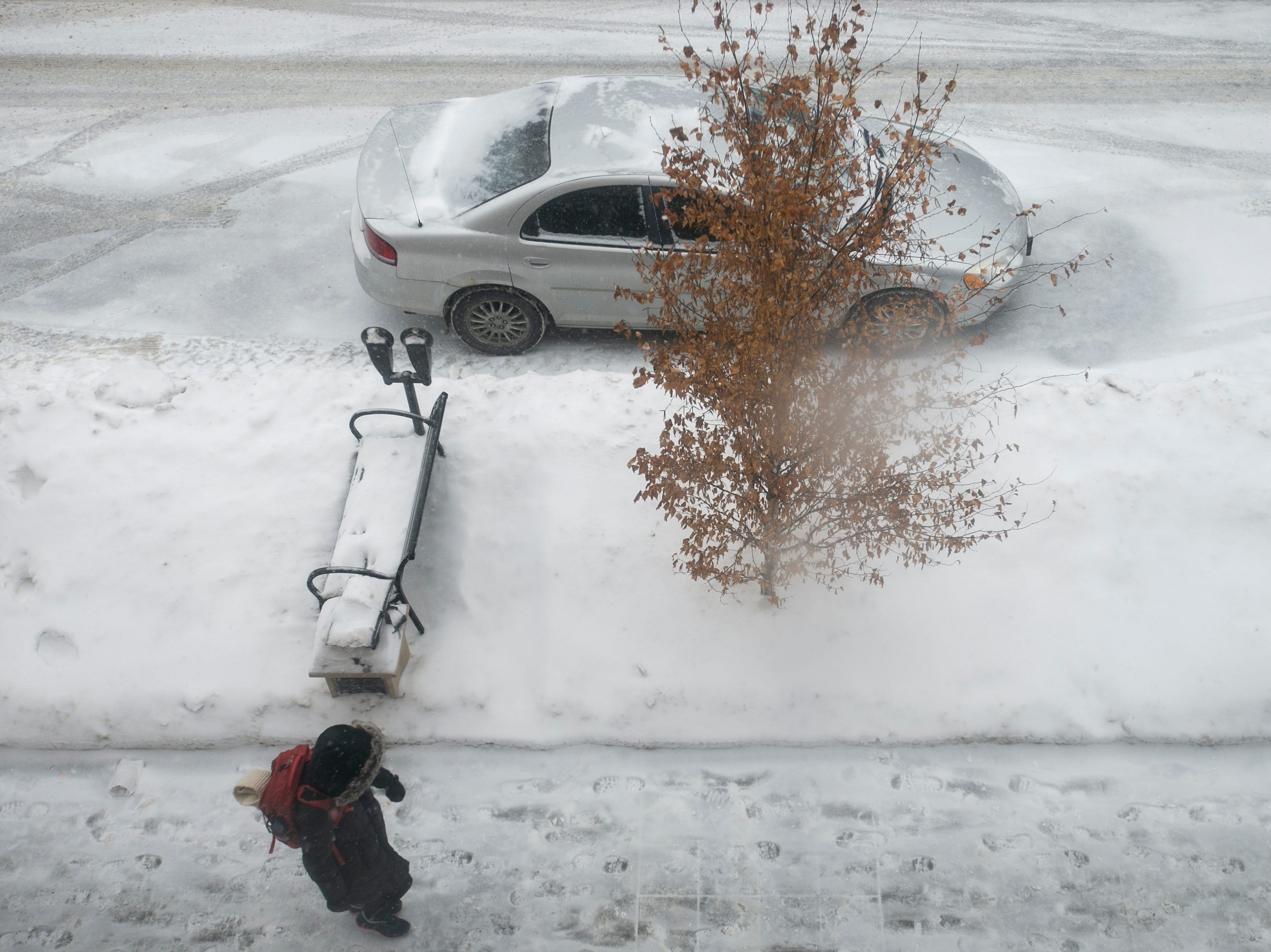 A person walks along Linn Street past a parked car as snow falls on Thursday, Jan. 31, 2019, in downtown Iowa City, Iowa.