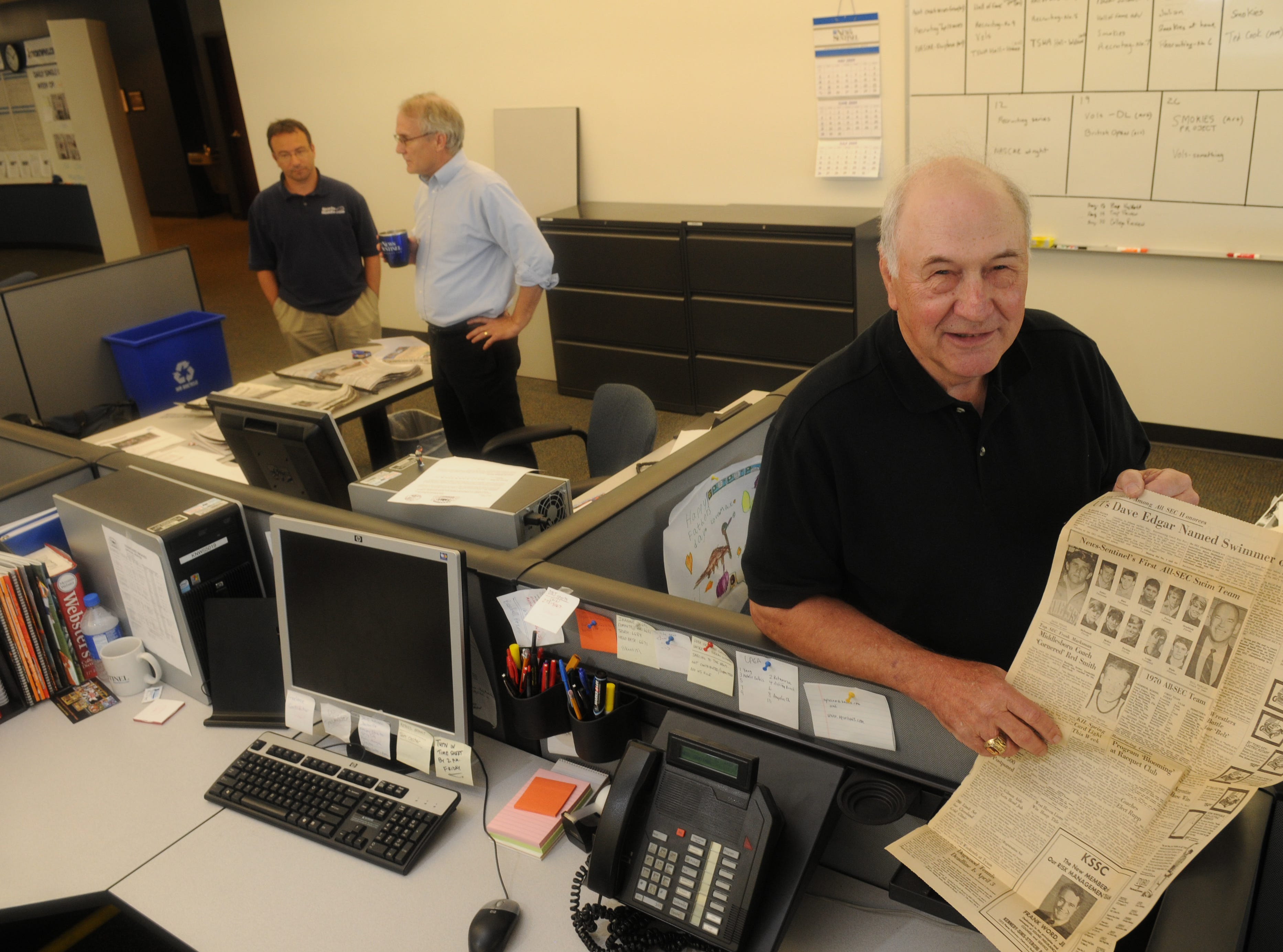 Retired KNS sportswriter Roland Julian visits the News Sentinel newsroom on  Thursday, July 2, 2009. Julian started at KNS on Aug. 29, 1957 and is now being inducted into the sportswriters Hall of Fame. At left are sports editors Phil Kaplan and Steve Ahillen. He holds a tear sheet from 1970 with the first News Sentinel All-SEC swim team, a feature he compiled team for 38 years.