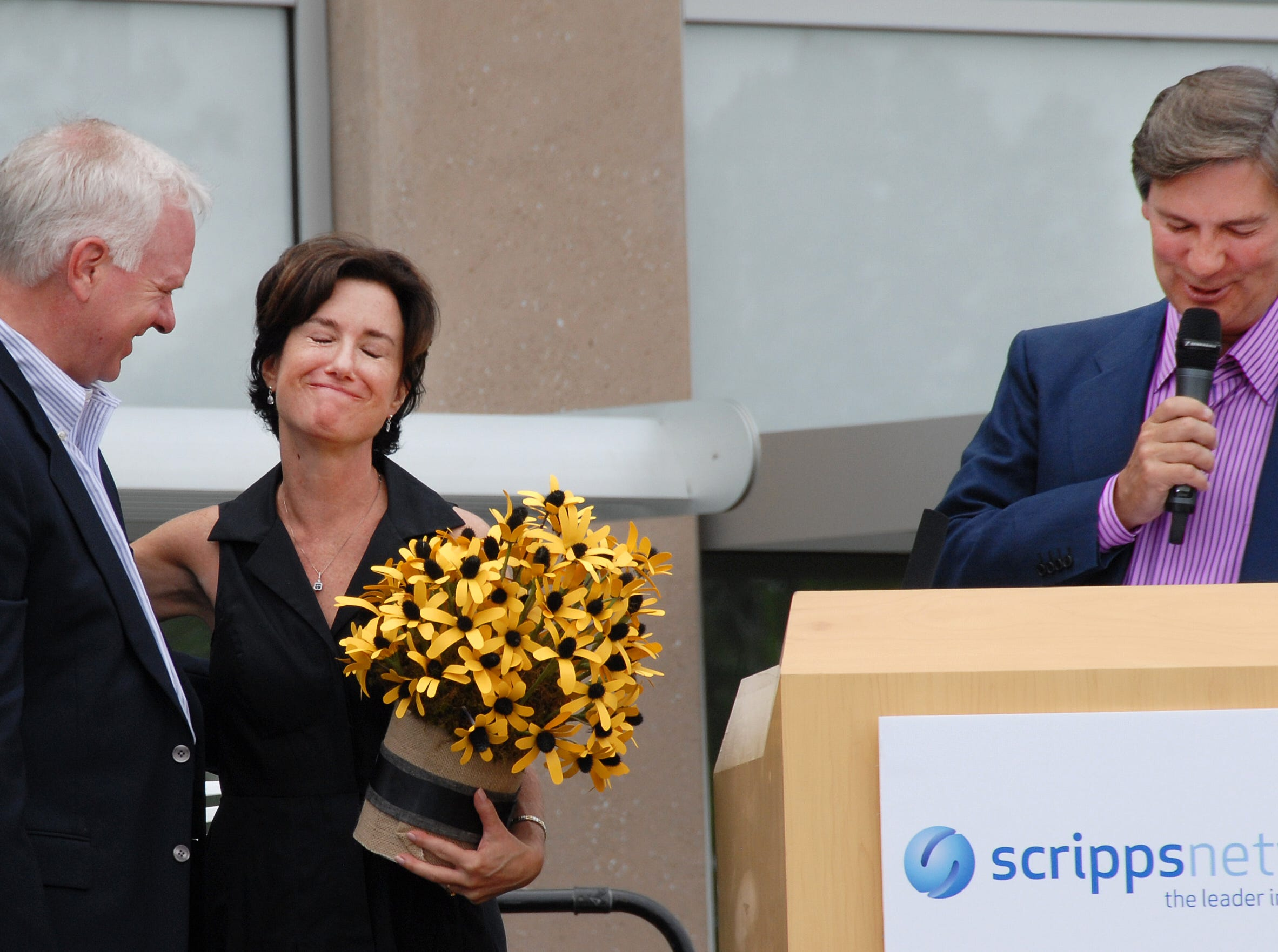 Scripps Networks President John Lansing left , and Scripps Networks Interactive CEO Ken Lowe, present Susan Packard, co-founder of HGTV and president of brand outreach for Scripps Networks Interactive, with flowers and the announcement of a park named for her 'Packard Park' on the grounds of the new 150,000-square-foot expansion of their headquarters Saturday May 15, 2010.