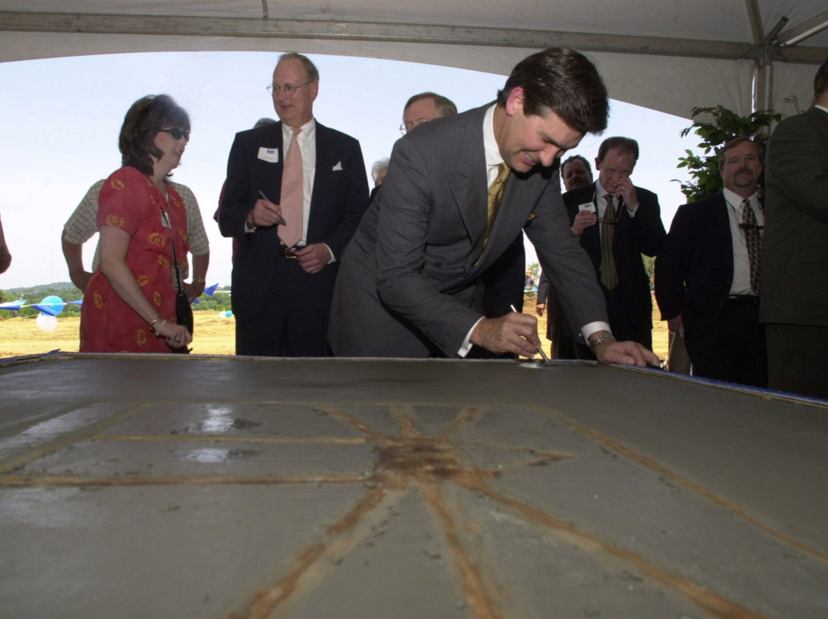In a May 17, 2001, photograph, E.W. Scripps Co. President and CEO Kenneth Lowe signs a commemorative concrete marker during a groundbreaking ceremony for the $50 million Knoxville News-Sentinel building. At left Angie Epps, News-Sentinel circulation sales and marketing manager, talks to Alan M. Horton, Scripps senior vice president for newspapers.