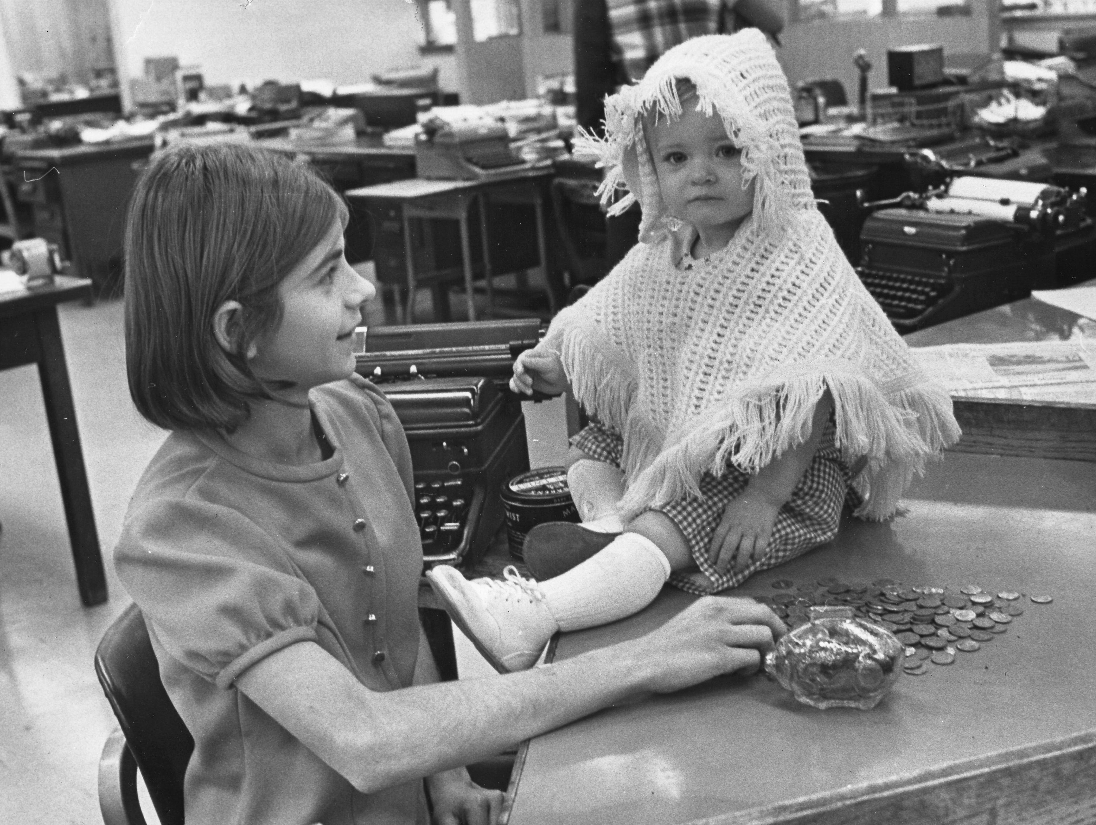 In a photograph published Dec. 14, 1970, Aequeta Meadows, left, counts the pennies in the News-Sentinel newsroom that were saved all year by her sister, Chasey, right, for the Empty Stocking Fund. Chasey contributed $5.55 towards the $10,958 that had been raised to date.