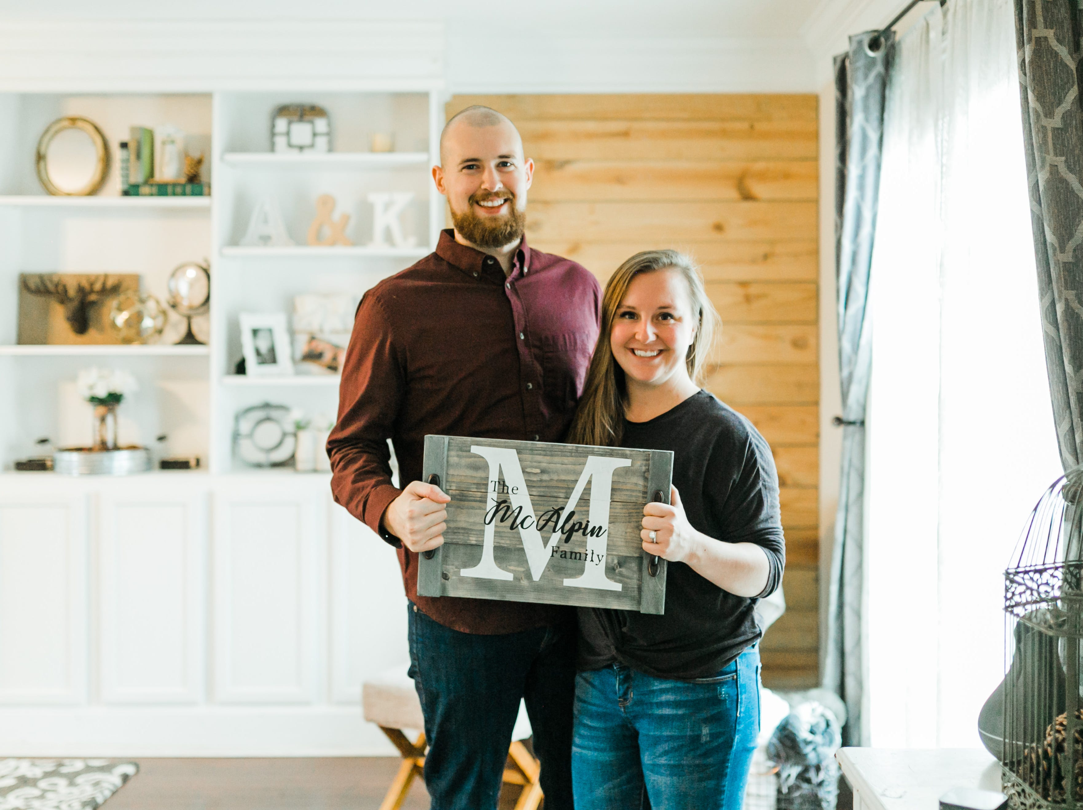 "Ashley and Kevin McAlpin, owners of McAlpin Creative, with one of their customized DIY trays. ""We do everything as a partnership,"" said Ashley. ""Kevin does the woodcutting and preparation. Then I do the vinyl stencil cutting and put the kits together. I also handle the marketing and getting our voice out there."""