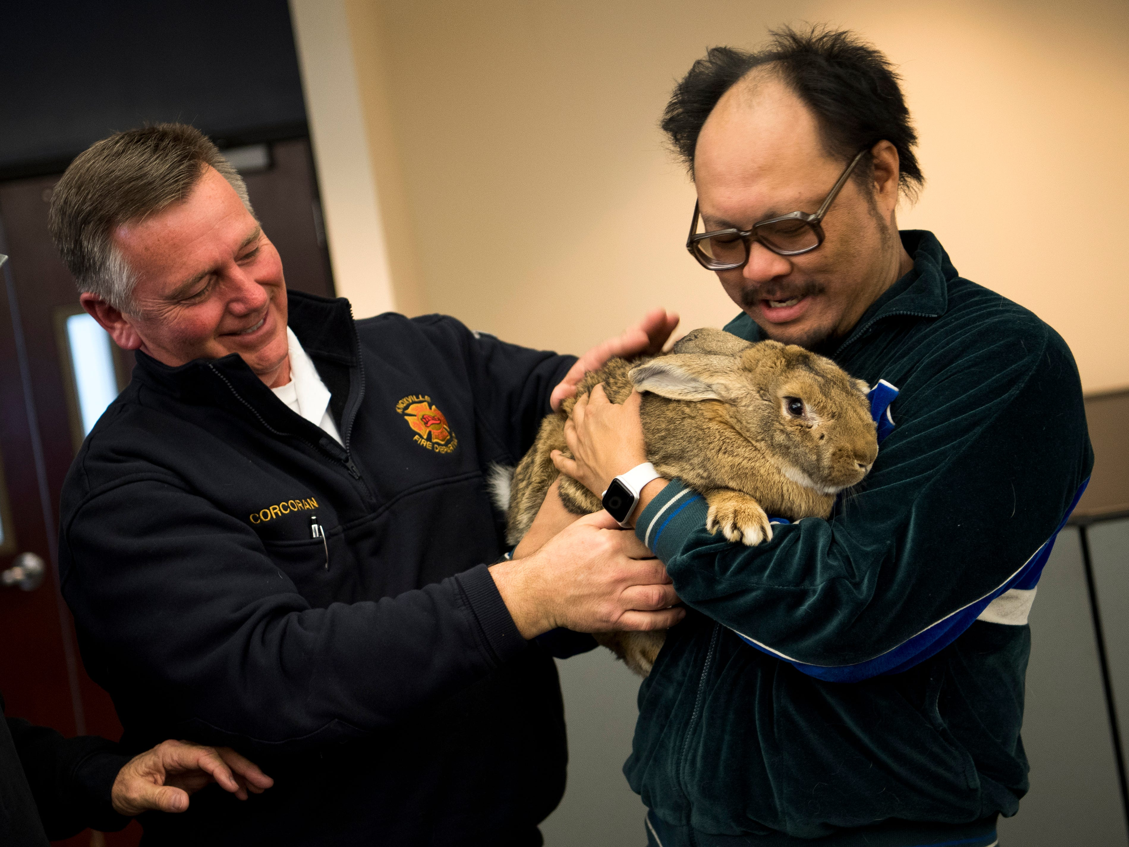 Knoxville Fire Department spokesman D.J. Corcoran, left, helps pet rabbit Barley into the arms of News Sentinel photographer Saul Young's arms in the News Sentinel's newsroom on Thursday, January 31, 2019.