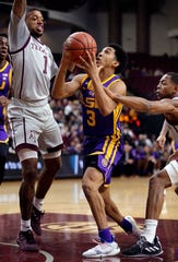 LSU guard Tremont Waters (3) is fouled by Texas A&M guard TJ Starks, right, as he drives past guard Savion Flagg (1) to the basket during the first half of an NCAA college basketball game Wednesday, Jan. 30, 2019, in College Station, Texas. (AP Photo/Michael Wyke)