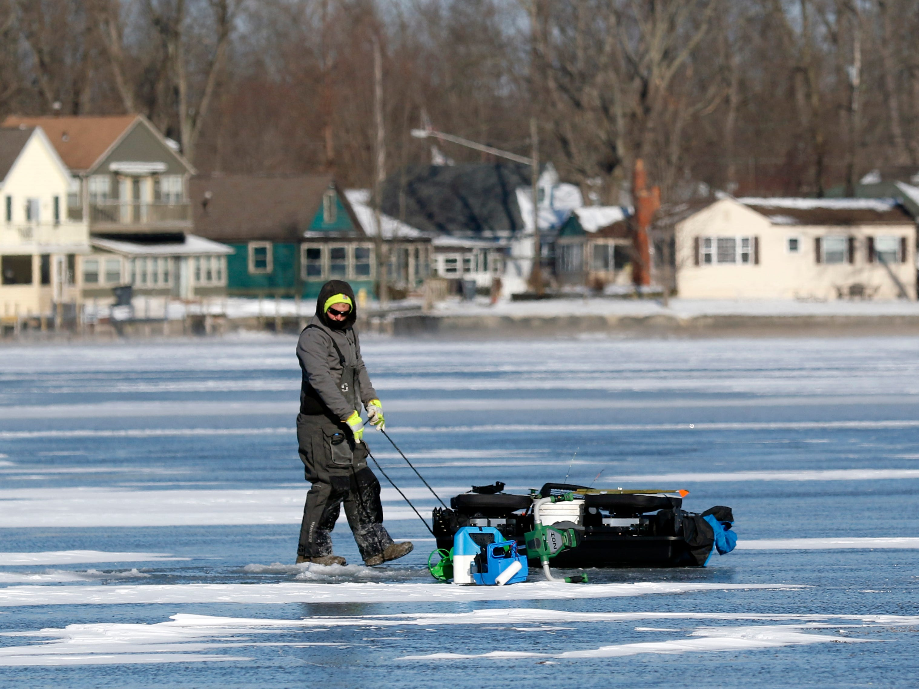 Jake Limings pulls his sled full of gear across the ice and snow covered surface of Buckeye Lake Thursday morning, Jan. 31, 2019. Freezing temperatures this week have formed more than five inches of ice on the lake's surface, and despite single digit temperatures and a wind chill advisory several people took the opportunity to ice fish.