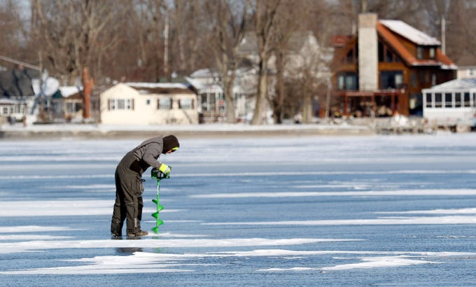 Jake Limings, from Marengo, drills a hole into the ice on Buckeye Lake Thursday, Jan. 31, 2019. Freezing temperatures this week have formed more than five inches of ice on the lake's surface, and despite single digit temperatures and a wind chill advisory several people took the opportunity to ice fish.