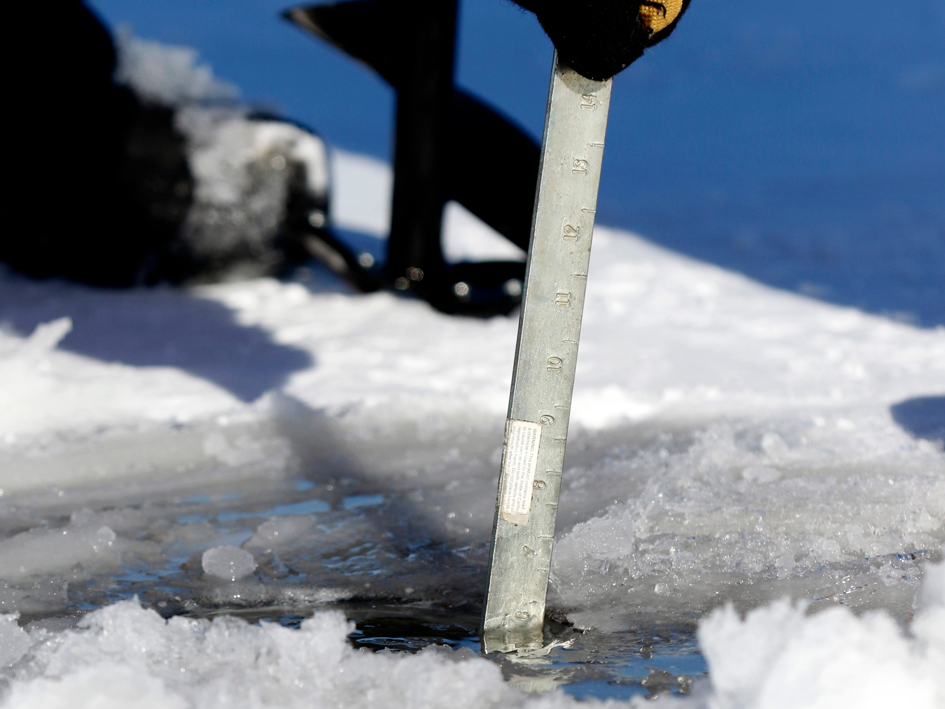 Dude Naeder, from Hamilton Township, uses a dipper to measure the thickness of the ice Thursday morning, Jan. 31, 2019, on Buckeye Lake. Freezing temperatures this week have formed more than five inches of ice on the lake's surface, and despite single digit temperatures and a wind chill advisory several people took the opportunity to ice fish.