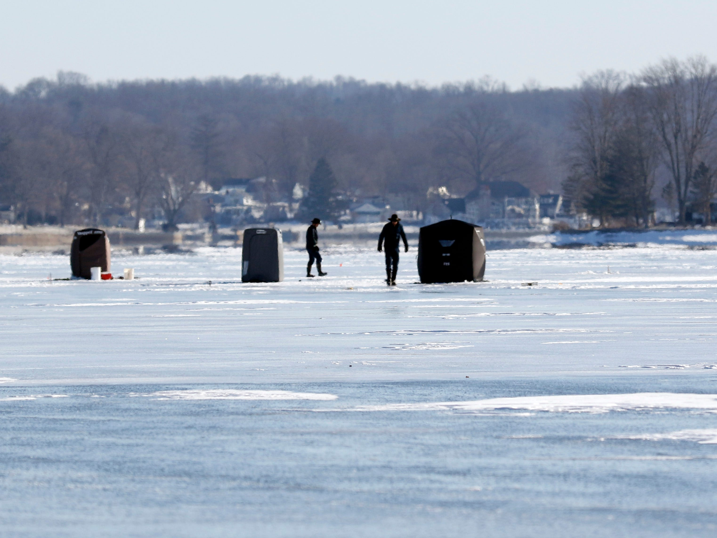 People walk among their shanties and tip-ups Thursday morning, Jan. 31, 2019, on Buckeye Lake. Freezing temperatures this week have formed more than five inches of ice on the lake's surface, and despite single digit temperatures and a wind chill advisory several people took the opportunity to ice fish.